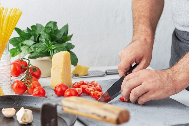 Szef kuchni gotuje makaron z pomidorami w kuchni