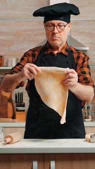 Szef kuchni gotuje ręcznie robiony makaron ze zdrowymi składnikami w domu w nowoczesnej kuchni. szczęśliwy starszy piekarz z bonete za pomocą drewnianego wałka do ciasta, posypując, przesiewając mąkę na stole, piecząc tradycyjne ciasteczka