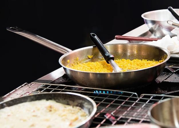 Szef kuchni gotuje risotto w kuchni w kuchni, gotuje risotto