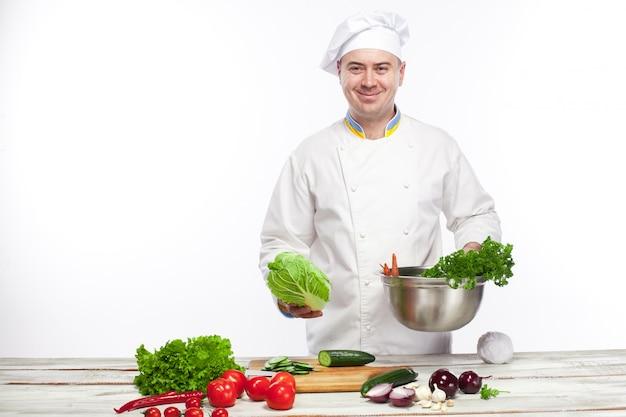 Szef kuchni gotuje sałatki ze świeżych warzyw w swojej kuchni