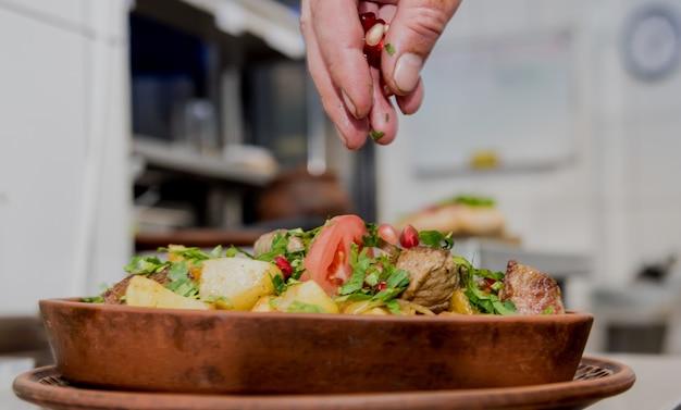 Szef kuchni gotuje smażone ziemniaki z kawałkami mięsa w kuchni restauracji