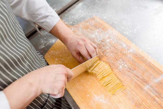 Szef kuchni gotuje spaghetti w restauracji