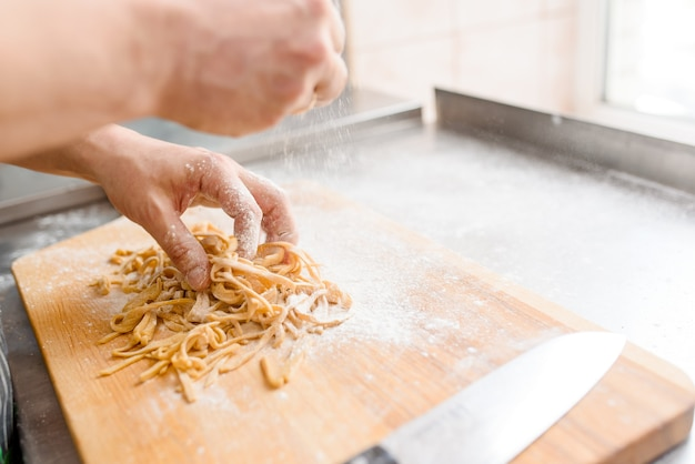 Szef kuchni gotuje surowy makaron z mąką do zupy ramen