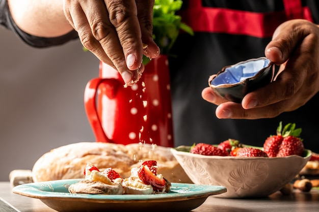 Szef kuchni gotuje tarty ze śmietaną, truskawkami i jagodami