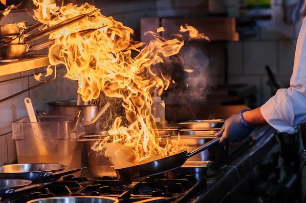 Szef kuchni gotuje w kuchni, restauracja gotowanie na ogniu z wokiem z bliska gotuj smażone warzywa w komercyjnej kuchni. syczuańskie chińskie jedzenie.