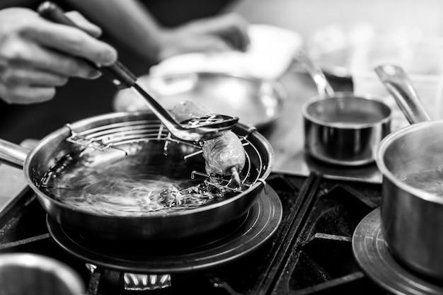 Szef kuchni gotuje w kuchni, szef kuchni w pracy, czarno-białe