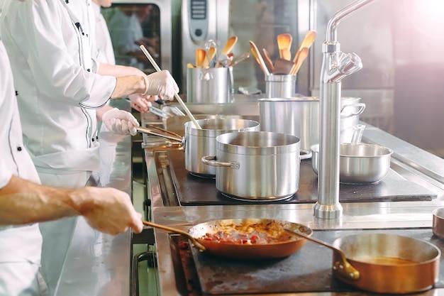 Szef kuchni gotuje warzywa na patelni wok. płytkie dof.