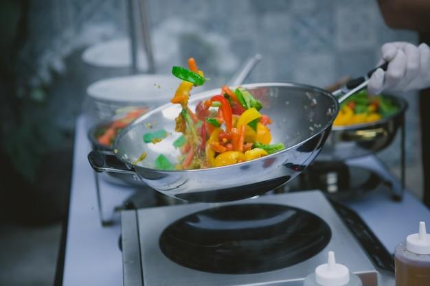 Szef kuchni gotuje warzywa na patelni wok.