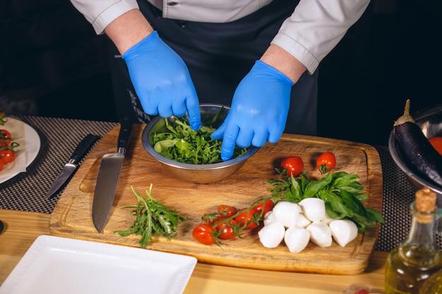 Szef kuchni gotuje wyśmienite danie mozzarelli z bazylią, pomidorami koktajlowymi i rukolą.