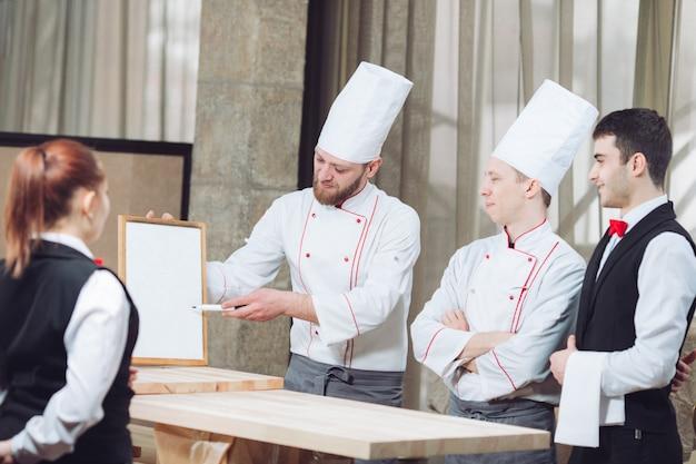 Szef kuchni i jego personel w kuchni. interakcja w kuchni komercyjnej.