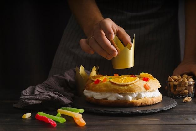 Szef kuchni kładzie papierową koronę na deser dnia objawienia