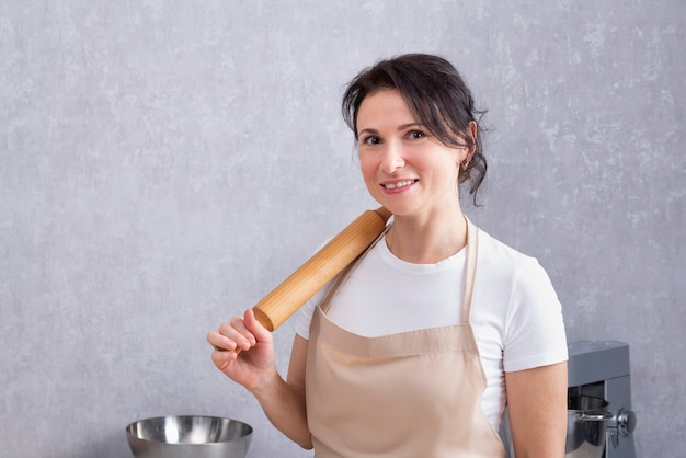 Szef kuchni kładzie wałek do ciasta na jej ramieniu i uśmiecha się do kamery.
