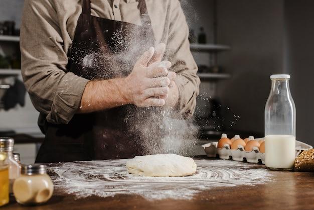 Szef kuchni klaszcze w dłonie mąką