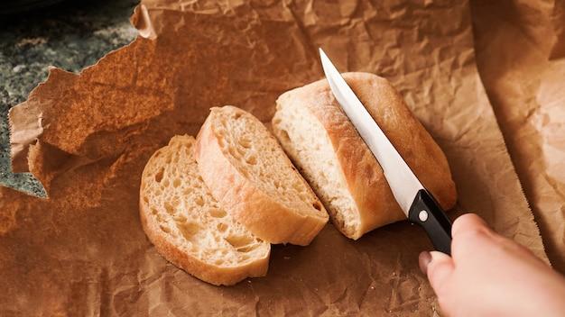Szef kuchni kroi ciabattę nożem w plastry ciabatty na papierze rzemieślniczym