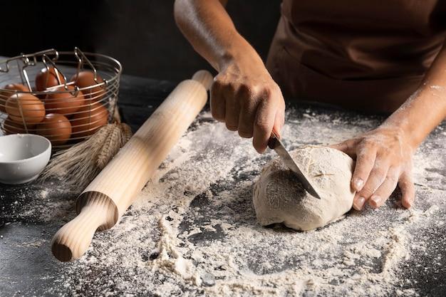 Szef kuchni kroi ciasto nożem
