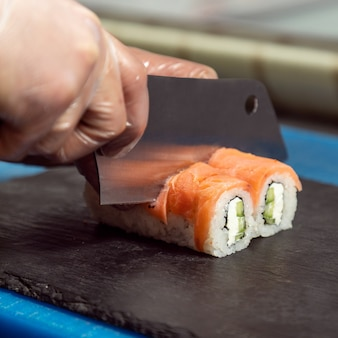 Szef kuchni kroi filadelfijską rolkę sushi z bliska