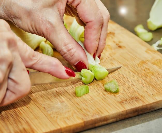 Szef kuchni kroi koper zgodnie z przepisem kulinarnym na drewnianej desce w kuchni.