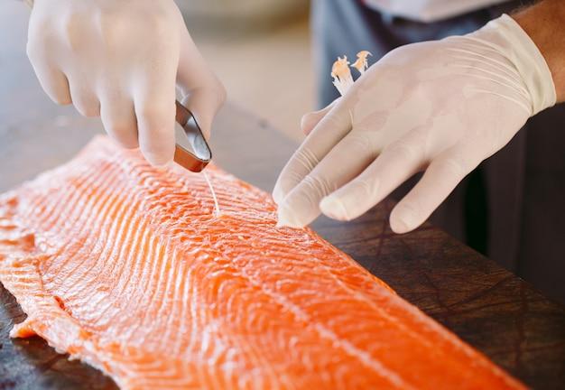 Szef kuchni kroi łososia na stole.