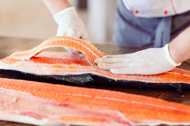 Szef kuchni kroi łososia na stole