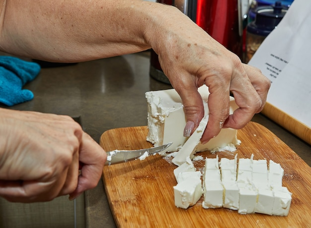 Szef kuchni kroi nożem ser feta, aby dodać go do sałatki. przepis krok po kroku.