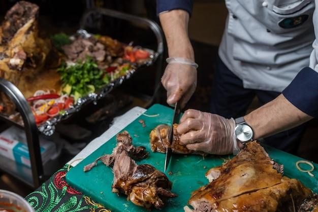 Szef kuchni kroi pieczoną wieprzowinę w restauracji