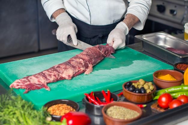 Szef kuchni kroi surowy stek wołowy od środka w kuchni