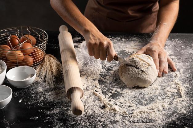 Szef kuchni krojenia ciasta chlebowego na stole