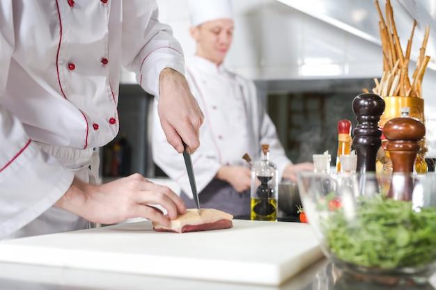 Szef kuchni krojenia mięsa na desce do krojenia, profesjonalny kucharz trzyma nóż i krojenia mięsa w restauracji
