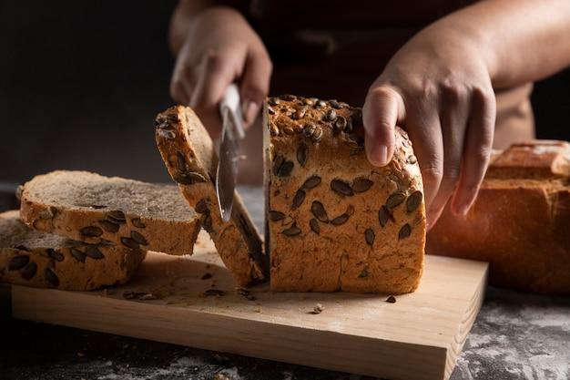 Szef kuchni krojenia pieczonego chleba nożem