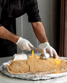 Szef kuchni łamie płonącą rybę ze skorupą solną ze stalowym zmiękczaczem