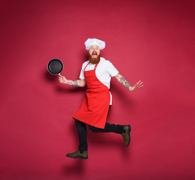 Szef kuchni mężczyzna boi się czegoś w tle w kolorze bordowym