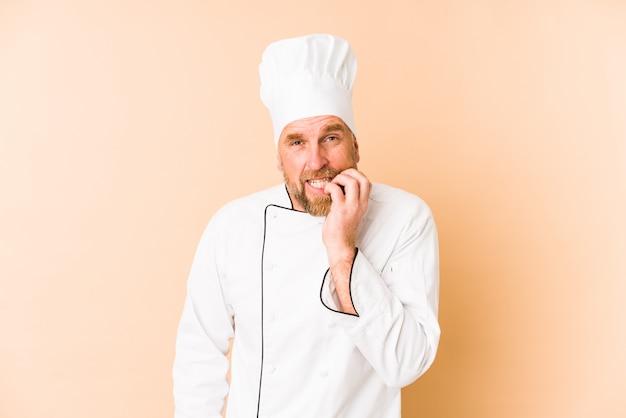 Szef kuchni mężczyzna na białym tle na beżowych obgryzających paznokciach, nerwowy i bardzo niespokojny.