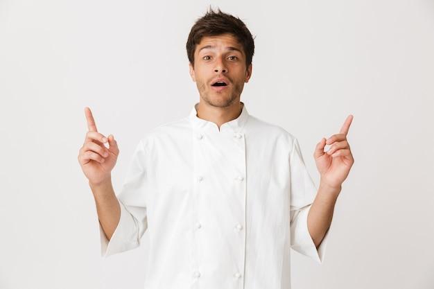 Szef kuchni mężczyzna stojący na białym tle na białej ścianie, wskazując na miejsce.