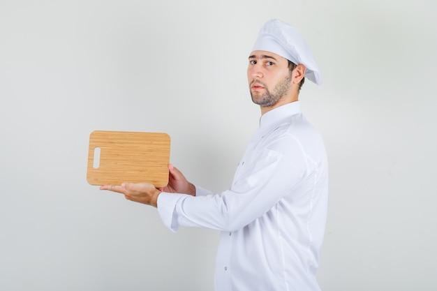 Szef kuchni mężczyzna w białym mundurze, trzymając drewnianą deskę do krojenia i patrząc surowo