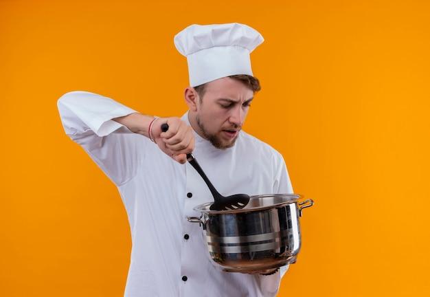 Szef kuchni mężczyzna w białym mundurze, trzymając srebrny garnek ze stali nierdzewnej z łyżką cedzakową na pomarańczowej ścianie