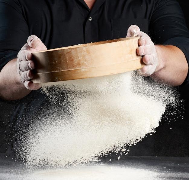 Szef kuchni mężczyzna w czarnym mundurze trzyma w rękach okrągłe drewniane sito i przesiewa białą mąkę pszenną na czarnej przestrzeni, cząsteczki lecą w różnych kierunkach, zakurzona przestrzeń
