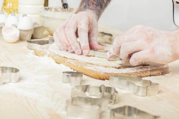 Szef kuchni mężczyzna w mundurze robi ciasteczka z formami do pieczenia