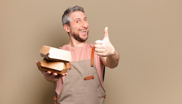 Szef kuchni mężczyzna w średnim wieku z hamburgerami