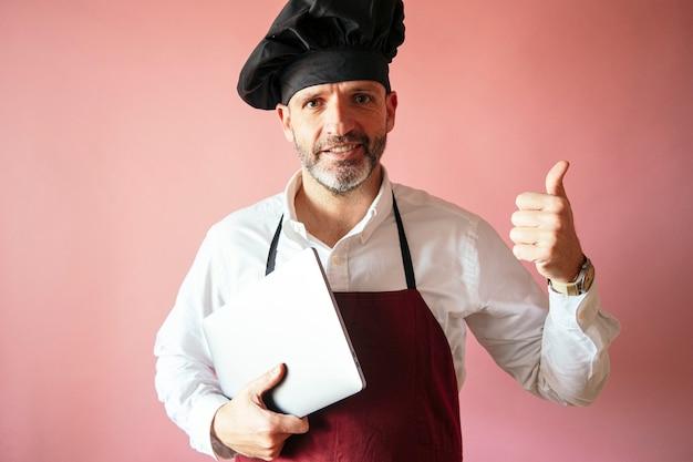 Szef kuchni mężczyzna z laptopa z różową ścianą