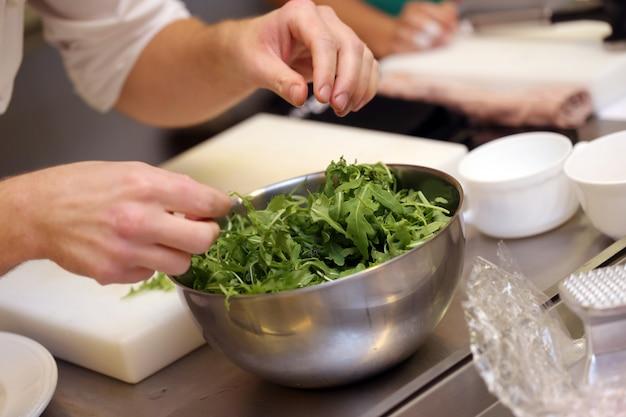 Szef kuchni miesza warzywa