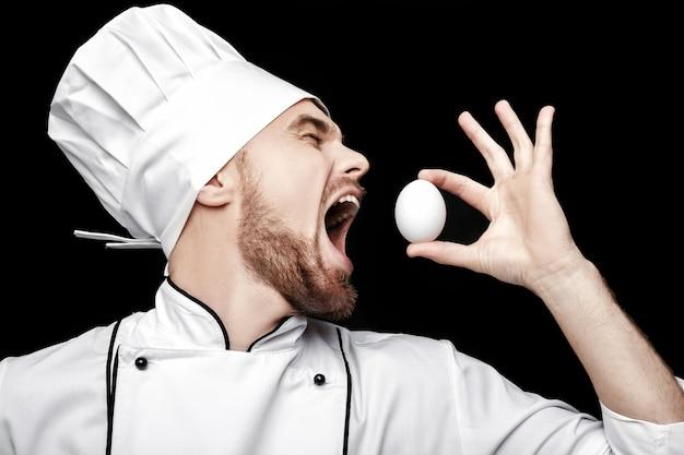 Szef kuchni młody brodaty mężczyzna w białym mundurze trzyma jajko na czarnym tle