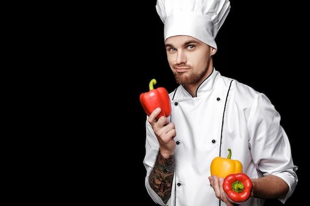 Szef kuchni młody brodaty mężczyzna w białym mundurze trzyma paprykę na czarnym tle