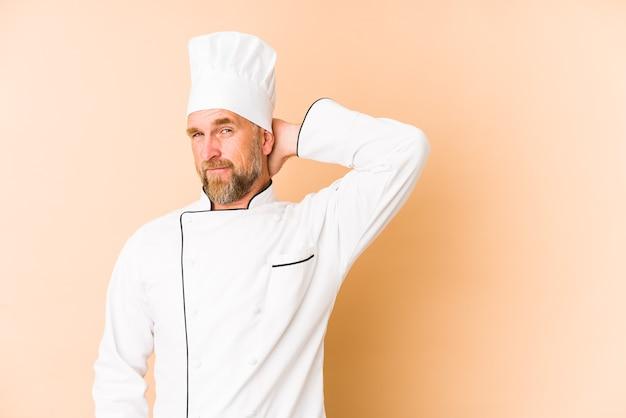 Szef kuchni na beżu dotykając tyłu głowy, myśląc i dokonując wyboru.