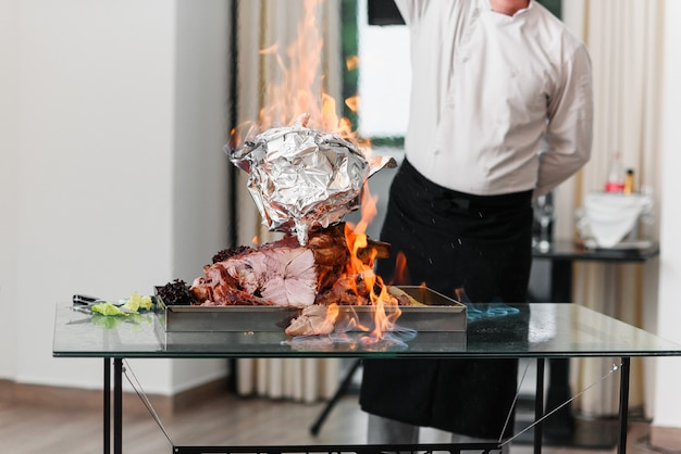 Szef kuchni nalewa alkohol do pieczonej turcji na półmisku w ogniu. pieczony indyk.