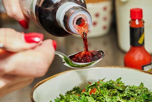 Szef kuchni nalewa łyżką syrop z granatów, aby dodać do sałatki