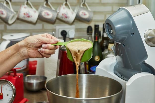 Szef kuchni nalewa spienione piwo z kadzi do miski