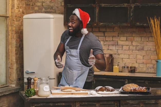 Szef kuchni nosi fartuch, przygotowuje ciasto na bochenek, używa różnych składników, w kuchni