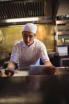Szef kuchni patrzy na listę zamówień w kuchni