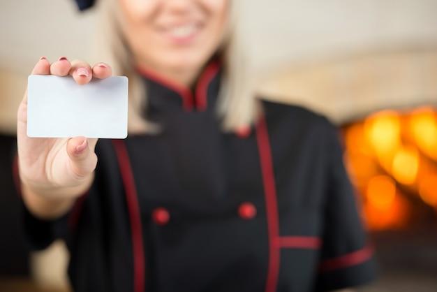 Szef kuchni piekarz pokazuje pustą wizytówkę.