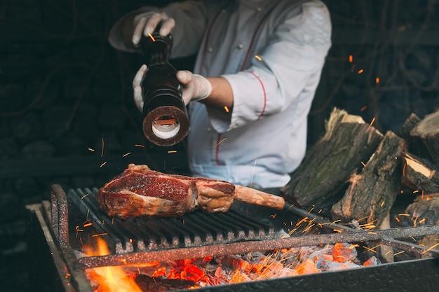 Szef kuchni pieprzy stek w ogniu.